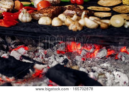 juicy vegetables and meat grilling. beef steak mushrooms corn pepper zucchini tomatoes garlic on grill. catering in food court at mall concept. space for text. weekend picnic