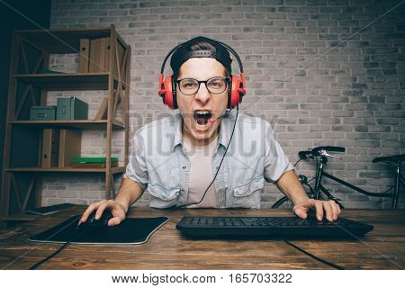 Young man playing game at home and streaming playthrough or walkthrough video. Screaming boy in headphones in front of computer trying to fight with his enemies.