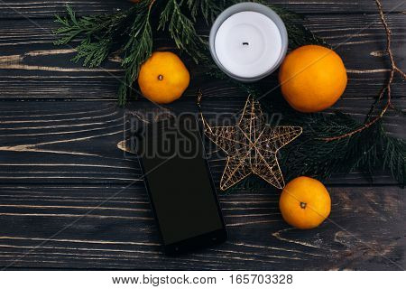 Christmas Flat Lay Phone With Empty Screen On Christmas Background Of Green Branches And Oranges And