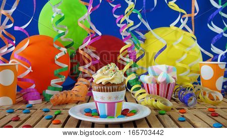 Cupcake on rustic wooden table with background of colorful balloons, plastic cups and candies with blue wall in background