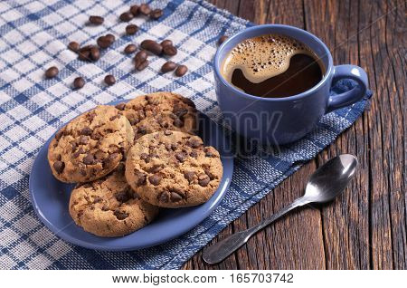 Cup of hot coffee and cookies with chocolate for breakfast on rustic wooden table. Blue tableware and tablecloth