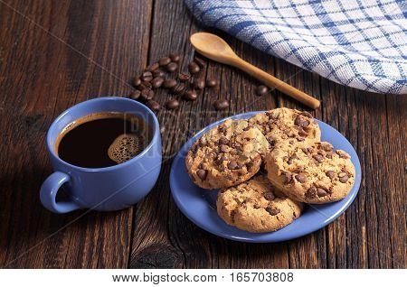 Blue cup of hot coffee and cookies with chocolate for breakfast on rustic wooden table