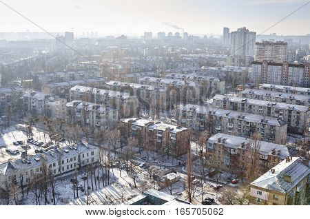 The aerial View of residential district Darnitsa in Kyiv, Ukraine in sunny winter day.View over the city rooftops with sunlight and snow.Moderns buildings at Industrial uptown, residential neighbourhood