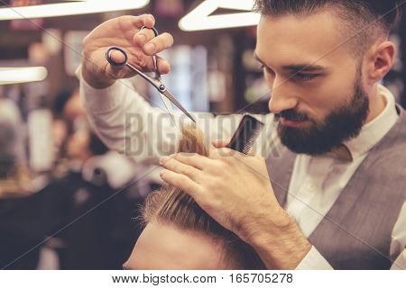 Attractive hairdresser is cutting his handsome client's hair at the barbershop