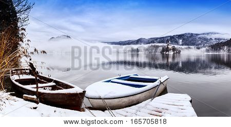 Snowy wooden boats on the backgorund of Church on the Island on Lake Bled Slovenia Europe. Winter landscape Bled Lake.