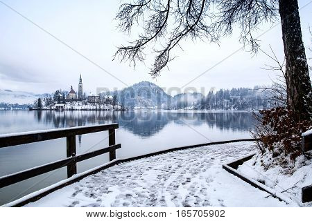 Snowy wooden Pier on the Alpine Lake Bled. Winter landscape. Travel Slovenia Europe. Bled Lake one of most amazing tourist attractions. View on snowy Island with Catholic Church.