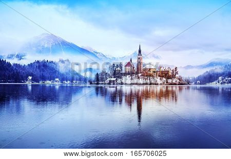 Winter landscape Bled Lake. Travel Slovenia Europe. Bled Lake one of most amazing tourist attractions. View on snowy Island with Catholic Church in Bled Lake with Castle and Alps in Background.