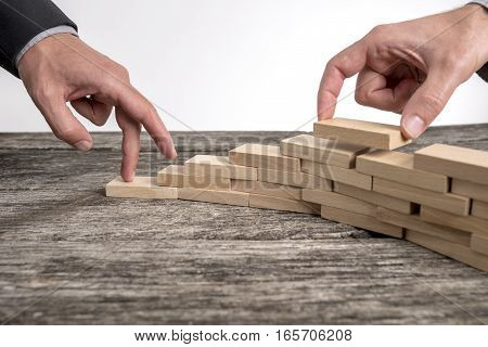 Fingers of businessman building wooden blocks in shape of upward trend graph on wooden table.
