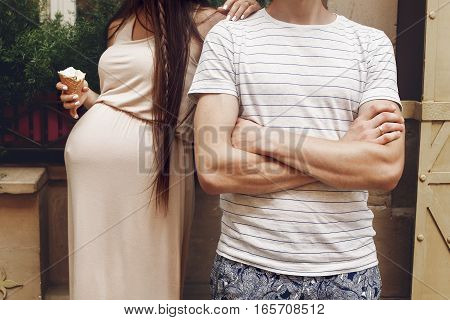Stylish Family Expecting For A Baby And Eating Ice-cream In Sunny Summer Street. Pregnant Woman With