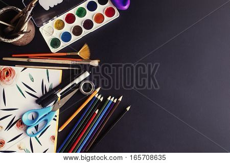 Back To School Concept, Colorful Pencils Paints Brushes Scissors And Notebook  On Chalkboard Backgro