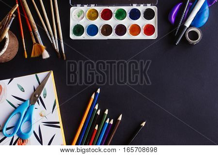 Colorful Pencils Paints Brushes Scissors And Notebook  On Chalkboard Background, Space For Text, Fla