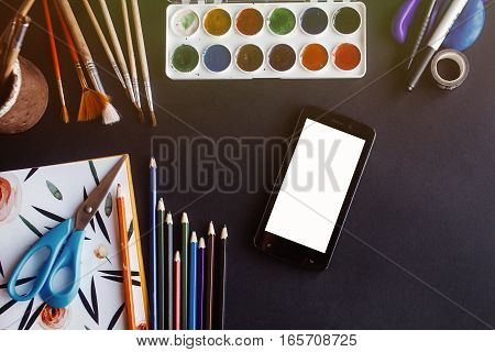 Smartphone Cell With Empty White Screen And Colorful Pencils Paints Brushes Scissors  On Chalkboard,