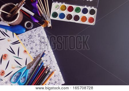 Colorful Pencils Paints Brushes Scissors And Coloring Book  On Chalkboard Background, Space For Text