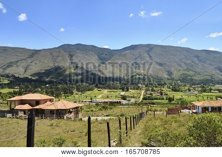 BOYACA COLOMBIA - JANUARY 23 2014: Nice view of residences along a vast field with mountains in the background next to Villa de Leyva in Colombia.