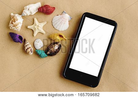 phone with empty screen and colorful shells on sandy craft background summer vacation travel concept space for text