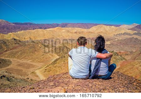 The young couple sits on the top of Zefahot Mount and gets enjoy of unique views Eilat Israel.