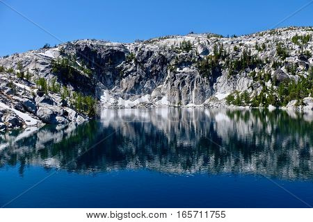 Granite cliff and reflection in alpine lake clear water. Lake Vivian. The Enchantments. Leavenworth. Seatte. WA. United States.