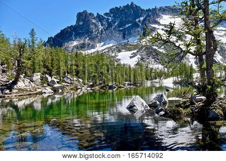 Sunlit alpine forest, clear lake and granite mountains. Leprechaun lake. The Enchantments. Cascade Mountains. Seattle. Leavenworth. WA. United States.