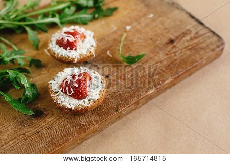 Delicious Fresh Canape With Gorgonzola Parmezan And Strawberry And Arugula On Wooden Desk On Craft B