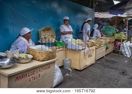 August 19 2016 Ibarra, Ecuador: indigenous women selling corn products in the local produce market