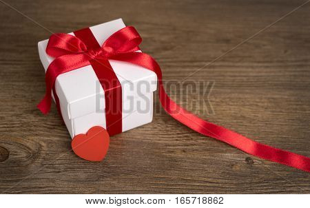 Gift box on the wooden background. Red ribbon. Valentine's Day gift.