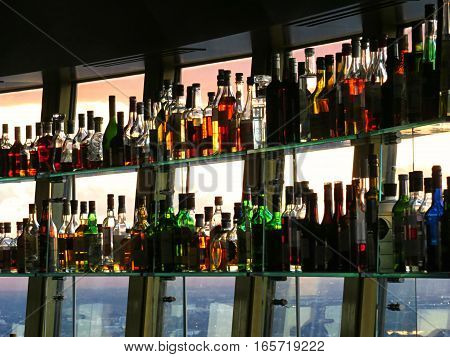 Sunlight through a row of glass cocktail alcohol bar bottles