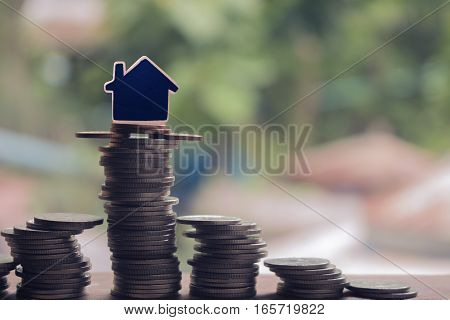 stack of coins witn house model concept idea for money save and purchase house.