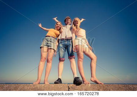 Friendship freedom summer holidays concept. Group of friends boy two girls spending time together having fun against sky wide angle view