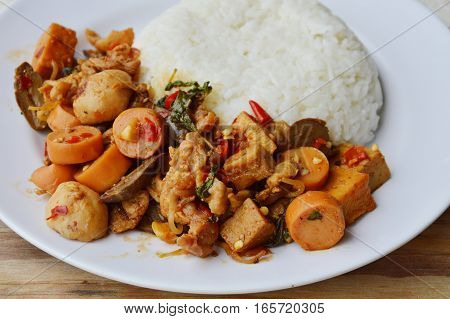 spicy stir fried mixed sausage and meat with basil leaf on rice