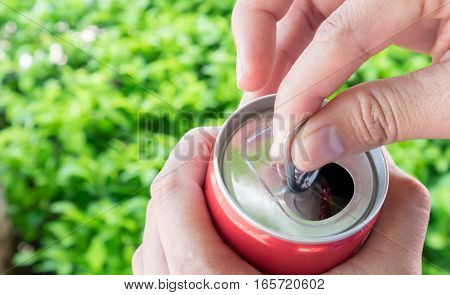 Closeup woman's hand open cola can with nature green blackground