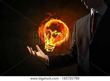 Close of businessman hand holding glowing fire light bulb icon