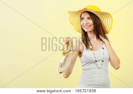 Woman In Big Yellow Summer Hat Holds Sandals