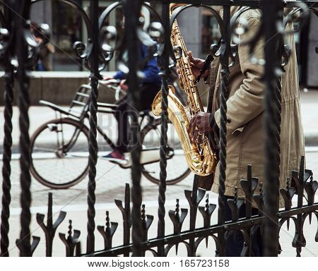 african street musician playing jazz on saxophone throw lattice with bicycle silhouette, city life in Amsterdam, lifestyle people concept close up