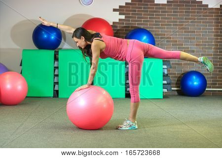 Young Beautiful White Girl In A Pink Sports Suit Does Physical Exercises With A Fit Ball At The Fitn