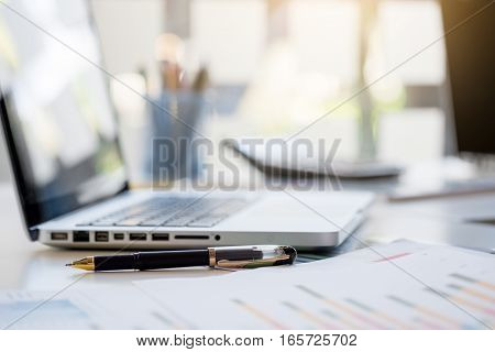 Business desk with a keyboard report graph chart pen and tablet on white table