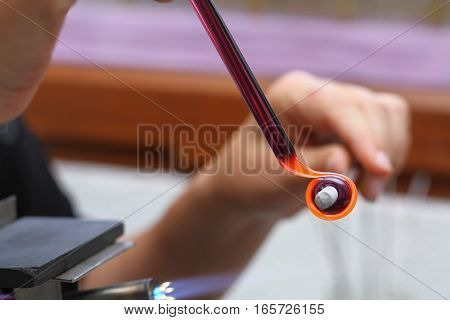woman's hands with tools for glass melting