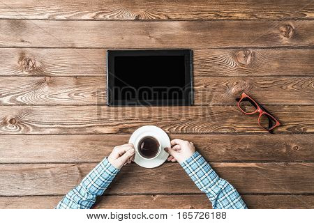 woman's hands holding a cup of coffee, glasses and tablet computer