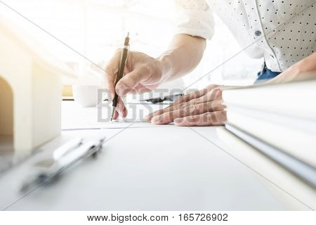 Close-up Of Person's engineer Hand Drawing Plan On Blue Print with architect equipment.