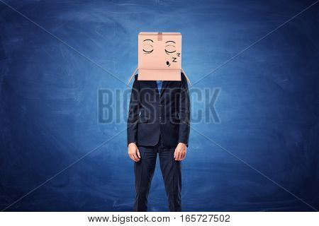 Businessman is wearing a cardboard box on his head with a sleepy face painted on it on blue blackboard background. Hidden emotions. Boring job. Everyday routine.