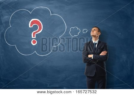Businessman on blue blackboard background where thoughts bubbles with a red question mark are drawn in chalk. Business and success. Business ideas. Questions and challenges.