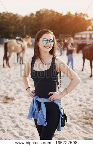 girl in sunglasses walking on the farm with horses