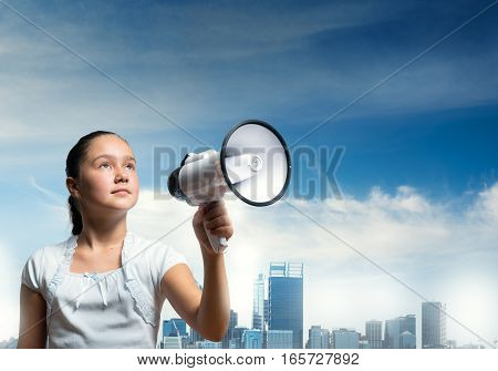 Girl of school age with megaphone on cityscape background