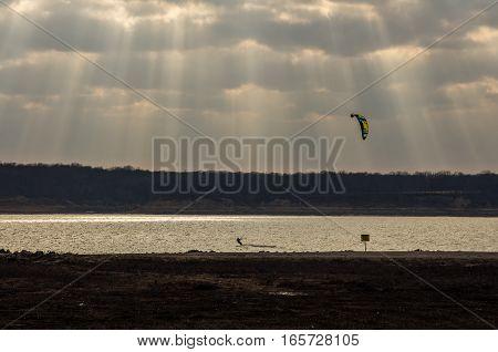 Kite boarder on a sun lit lake