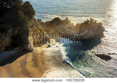 Late afternoon environment of McWay Falls in Big Sur California. Pacific ocean coastline. Water fall pour into the sea.