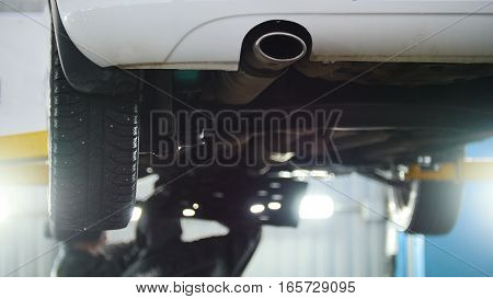 Car service - mechanic unscrewing automobile device while working under a lifted car, exhaust pipe, close up