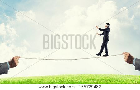 Businessman with blindfolder on eyes walking on rope over natural background