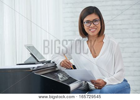 Smiling beautiful female Asian musician writing music