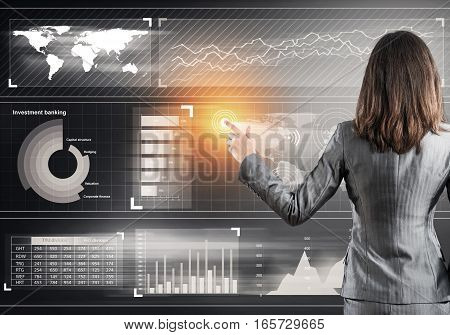 Rear view of businesswoman working with virtual panel interface