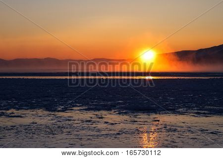 Sun just over surface of freezing lake in mist from vaporization just before sunset