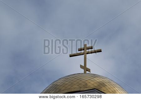Close up of a gold toned onion dome with an Orthodox cross on top. The dome is on the Church of All Saints in Yekaterinburg Russia on the site of the execution of the Romanovs.